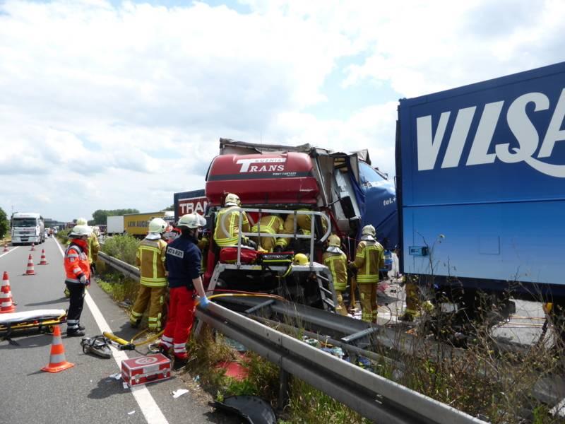 Einsatzkräfte beim Befreien des eingeklemmten Fahreres mit Hilfe von hydraulischem Rettungsgerät.