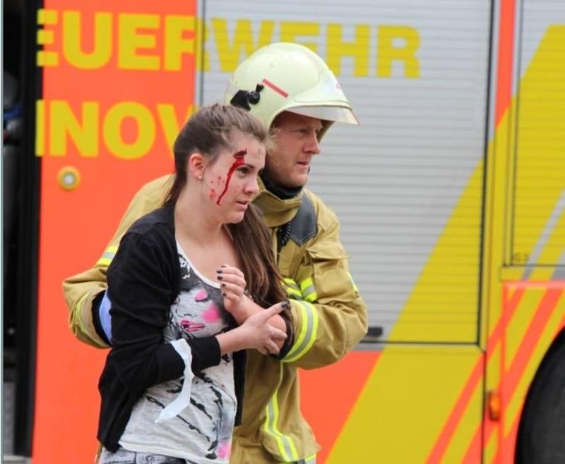 Eine Verletzte wird von einer Einsatzkraft dem Behandlungsplatz zugeführt