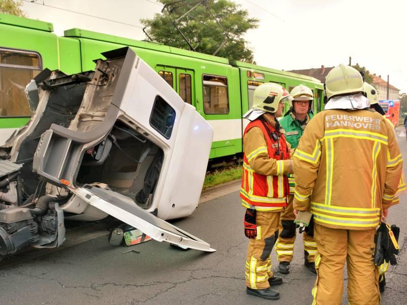 Mehrere Einsatzkräfte der Feuerwehr Hannover vor dem umgeschlagenen Führerhaus des LKWs und der Stadtbahn.