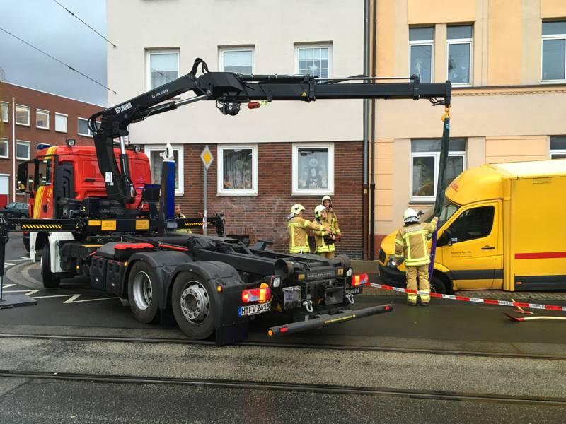 Mehrere Einsatzkräfte der Feuerwehr Hannover am Wechselladerfahrzeug mit Kran, bei der Bergung des Lieferwagens.