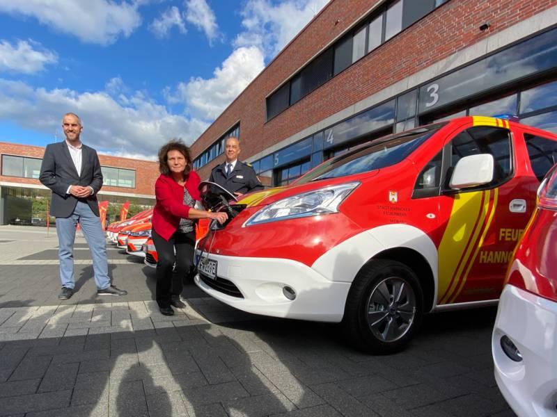 Ein E-Fahrzeug der Feuerwehr Hannover mit Personen im Vordergrund