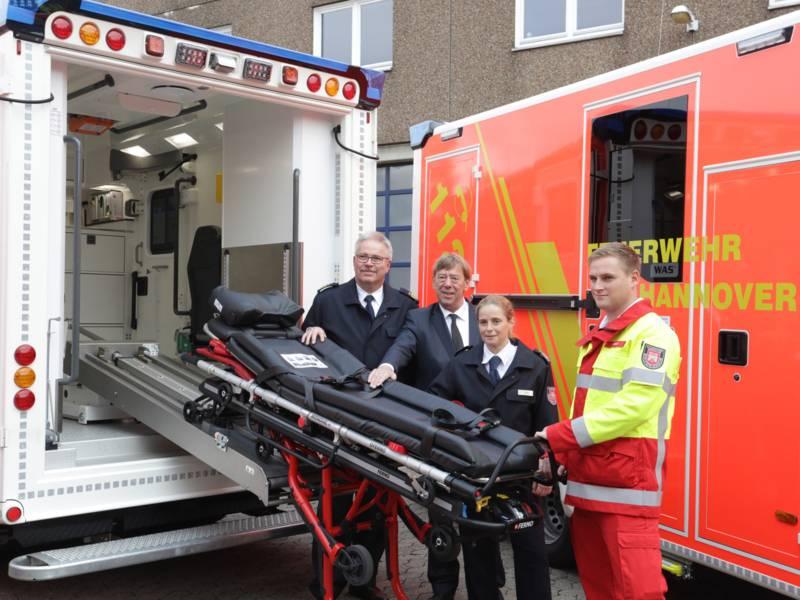 Feuerwehrchef Claus Lange, Feuerwehrdezernent Harald Härke, Schulleiterin Jeanette Mirande und Notfallsanitäter Andre Schmidt zeigen die automatische Einzughilfe für Fahrtragen an den neuen Rettungswagen.