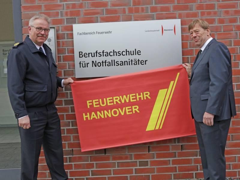 Feuerwehrdezernent Harald Härke und der Direktor der Feuerwehr Claus Lange enthüllen das neue Schild an der Berufsfachschule.