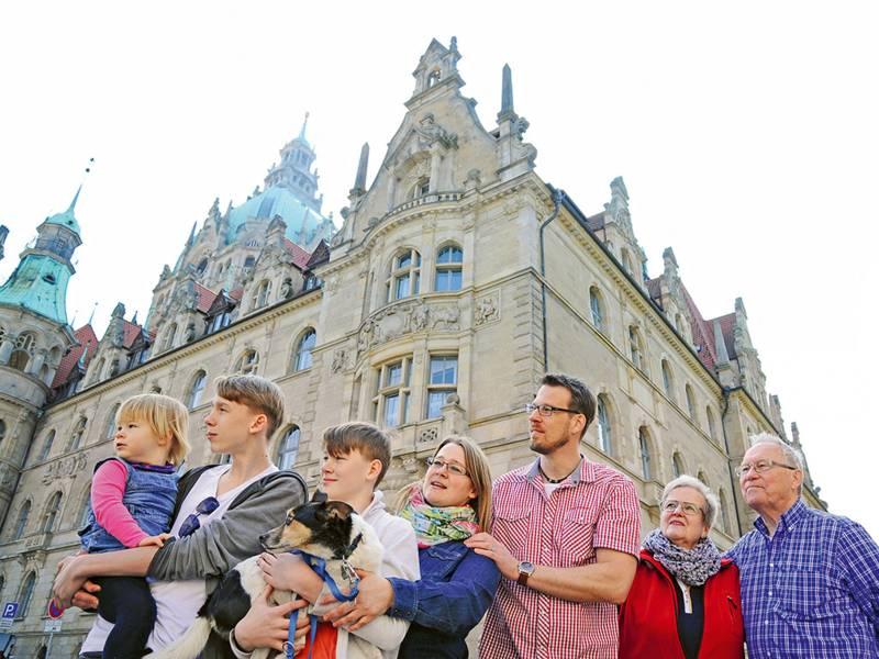 Eine Familie bestehend aus drei Generationen und einem Hund vor dem Rathaus in Hannover