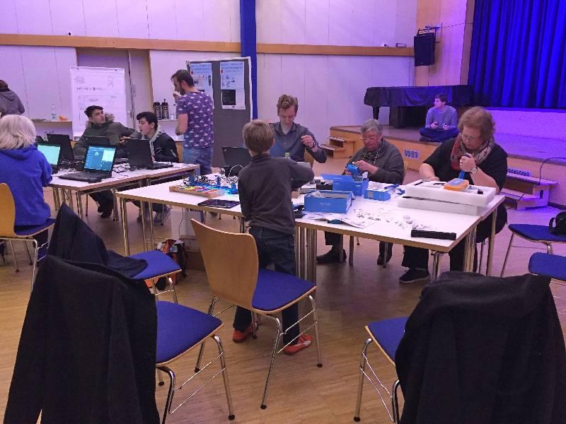 In einem blau ausgeleuchteten Raum sitzen Personen unterschiedlichen Alters an Tischen und arbeiten handwerklich mit Computern.