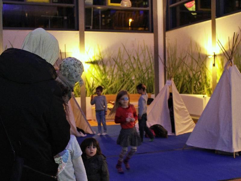 Kinder toben unter Beaufsichtung um kleine Zelte herum, die im Freizeitheim aufgestellt sind.