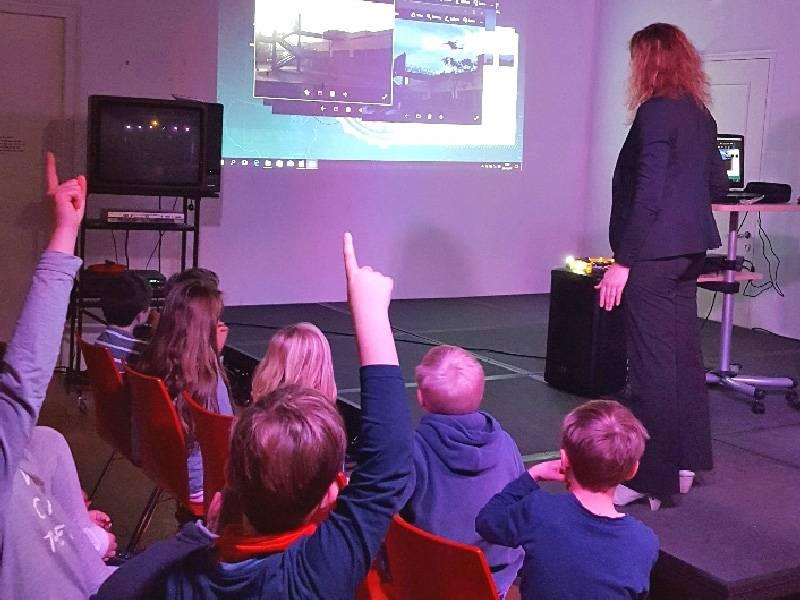 Kinder, die auf Stühlen sitzen, lauschen und beteiligen sich an einem Vortrag, bei dem eine Referentin über einen Beamer Bilder zeigt.