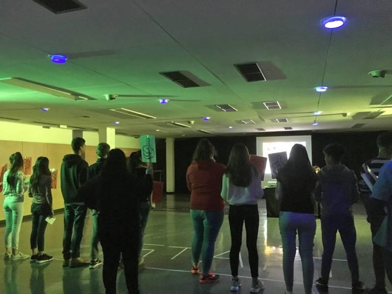 """Jugendliche stehen in einem abgedunkelten Raum und halten Schilder mit dem Daumensymbol für """"Liken"""" in die Höhe als Reaktion auf etwas, was auf der Leinwand im Saal gezeigt wird."""