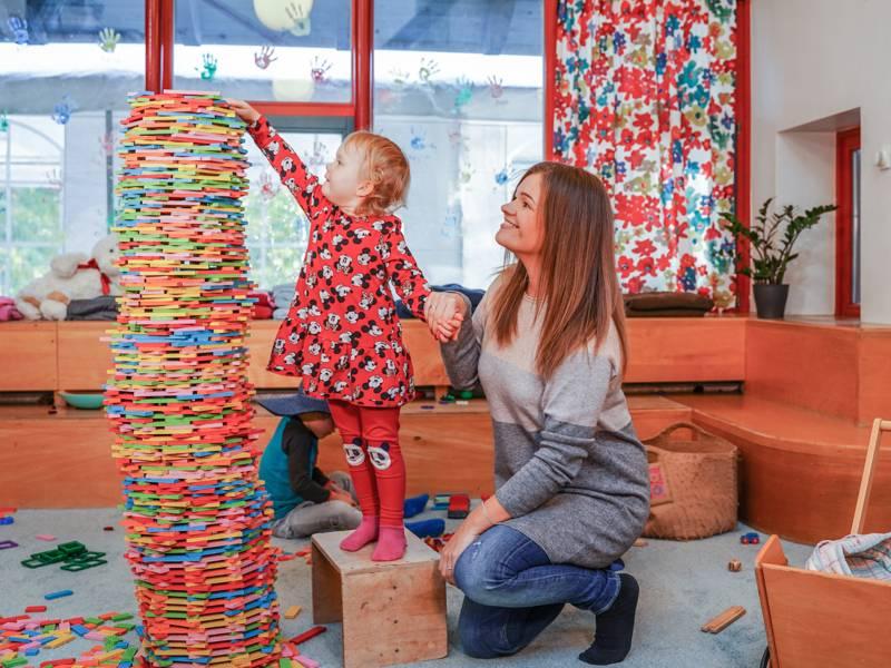 Ein Kind stapelt etwas, eine Frau hockt dahinter und hält dem Kind eine Hand