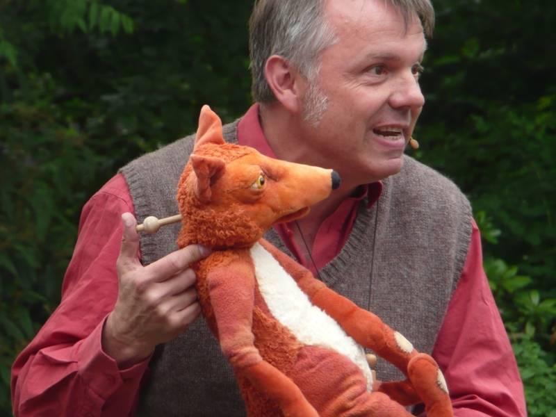 Ein Puppenspieler mit einem Fuchs als Stockhandpuppe