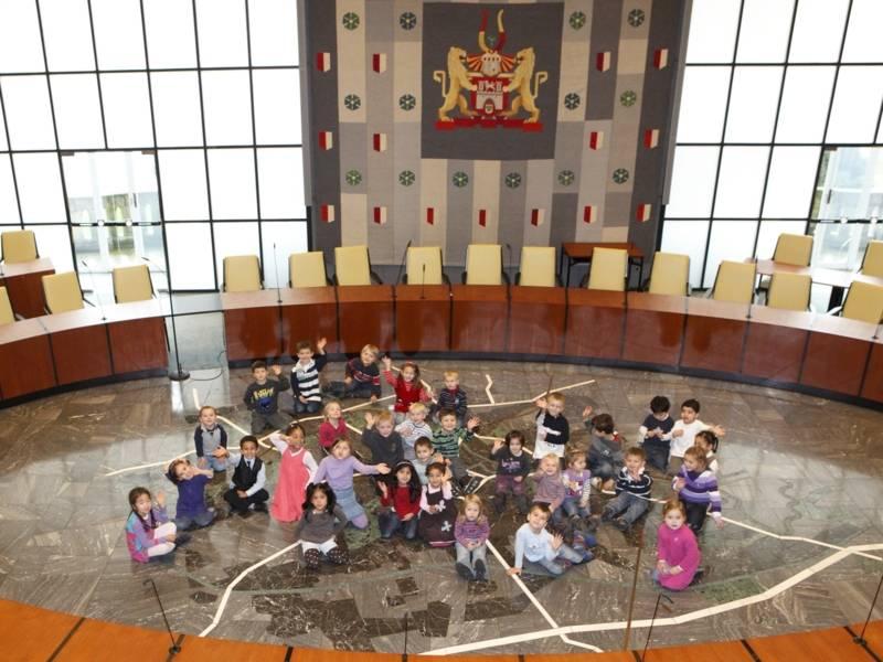 Kinder sitzen im Ratssaal auf dem Boden und winken.