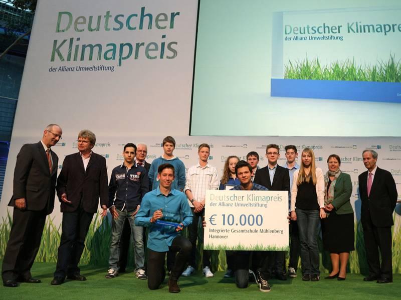 """Eine Bühne, auf der mehr als ein dutzend vor allem junge Personen stehen, zwei von ihnen halten die Auszeichnung mit dem """"Deutschen Klimapreis"""" in den Händen"""