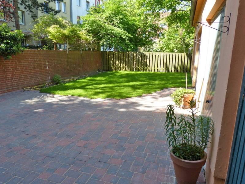 Entsiegelter Innenhof mit Grasfläche, bei dem Regenwasser durch die Fugen der Pflastersteine abfließen kann.