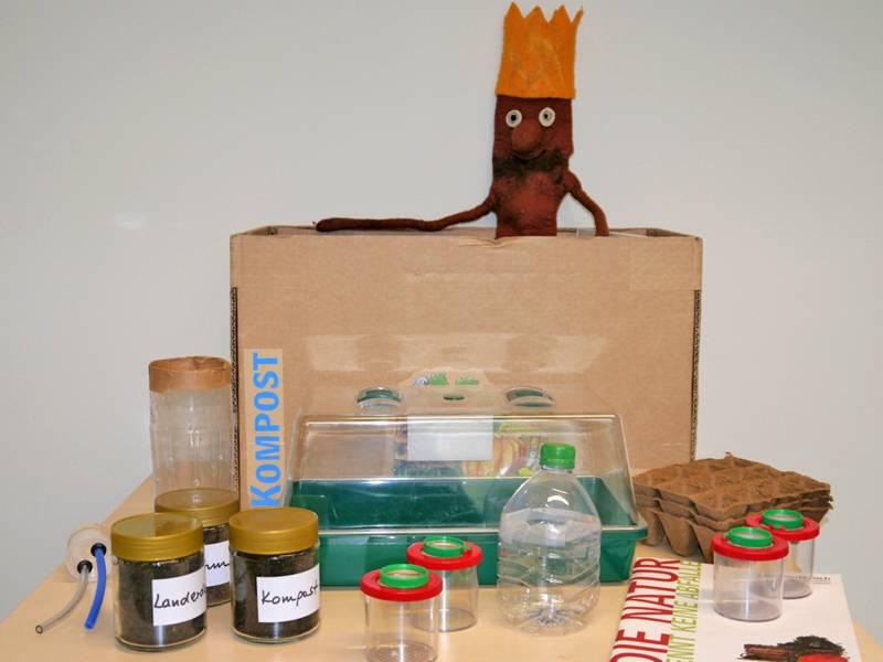 """Gläser, Anzuchtbehälter, Broschüre und eine Puppe gehören unter anderem zum Unterrichtsangebot """"Aktivkiste Kompost""""."""