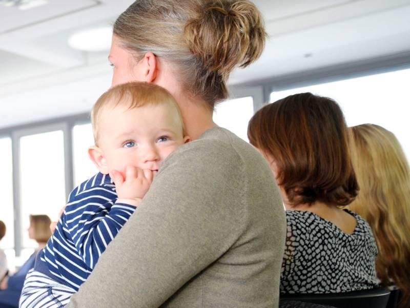 Ein Baby auf dem Arm einer Frau, im Hintergrund weitere Frauen
