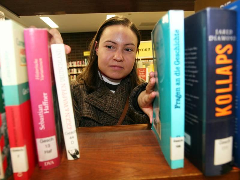 Eine Frau guck durch eine Lücke in einem Bücherregal.