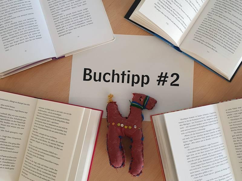 """Verschiedene Bücher liegen aufgeklappt um ein Schild mit der Aufschrift """"Buchtipp #2"""" herum. Auf diesem Schild liegt ein kleines Kuscheltier."""