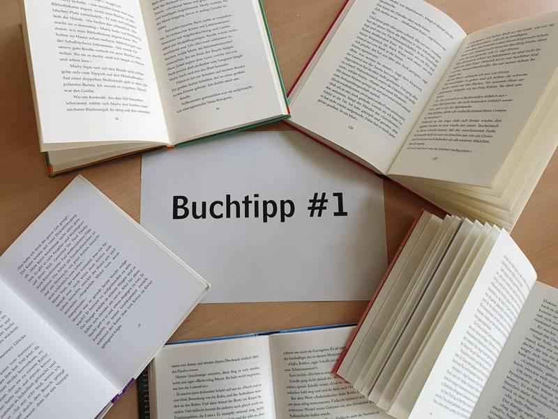 """Die Aufschrift """"Buchtipp #1"""" umrandet von aufgeschlagenen Büchern."""