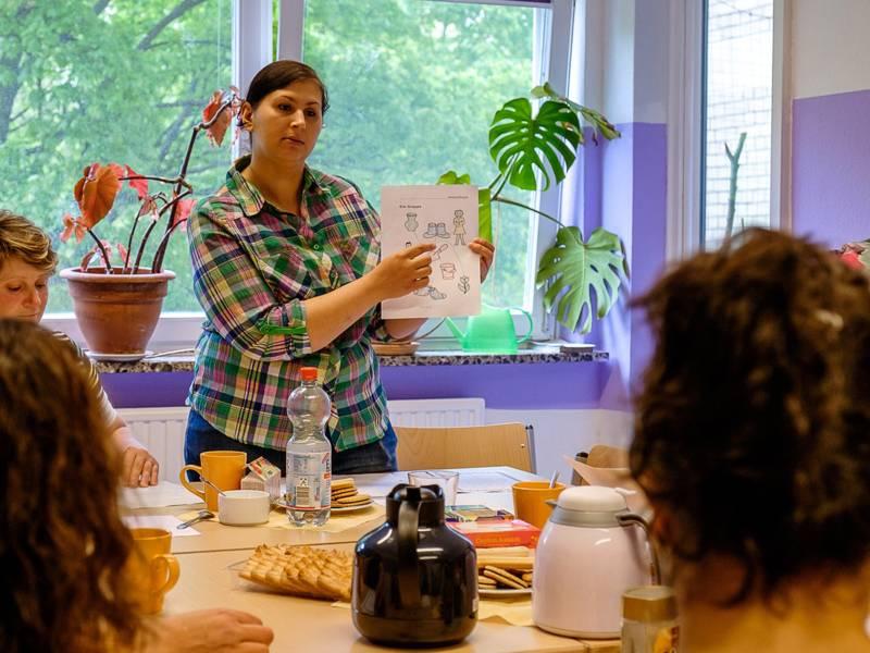 Eine Frau steht an einem Tisch, an dem weitere Personen sitzen, und zeigt etwas auf einem Blatt Papier.