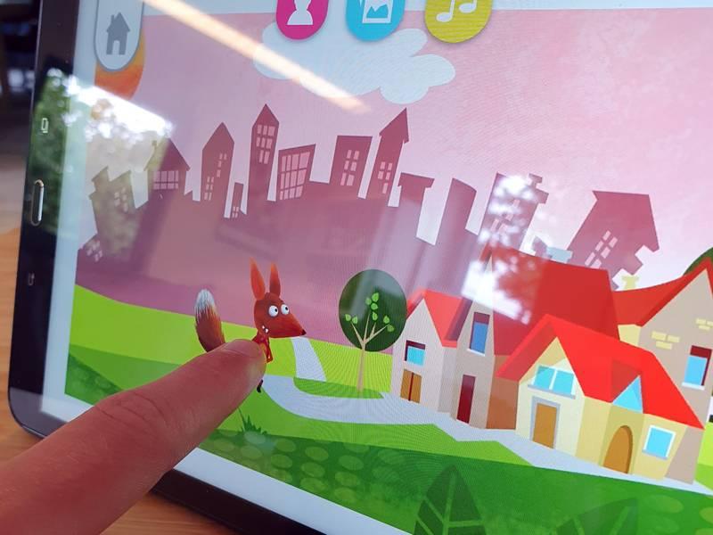 Ein Finger zeigt auf ein Tablet, auf dem ein Videospiel für Kinder läuft.