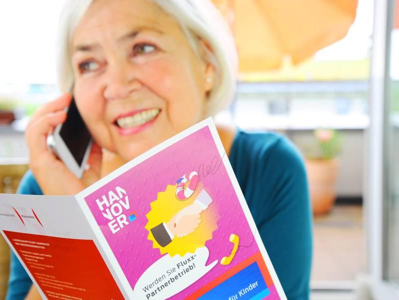 Eine Frau hat in der einen Hand eine Broschüre und in der anderen Hand ein Handy am Ohr.