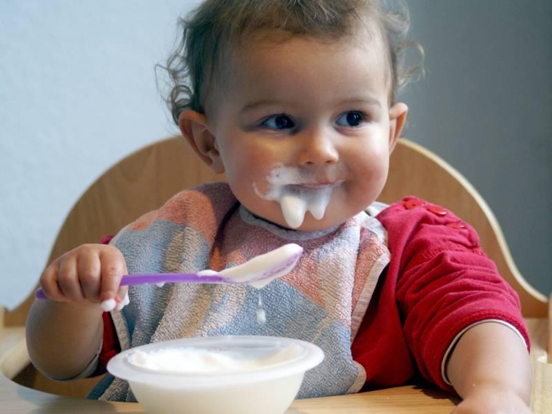 Ein kleines Kind isst Brei.
