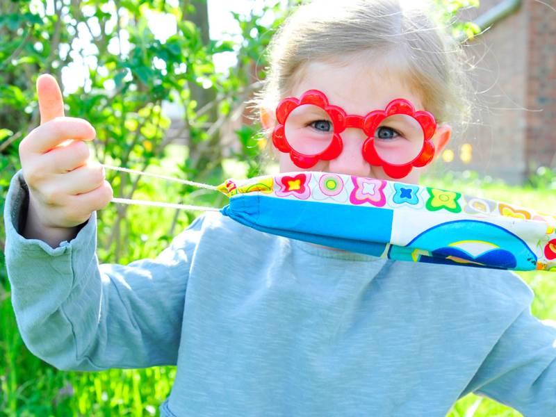 Kind mit roter Brille in Form von zwei Blumen und mit bunter Maske.