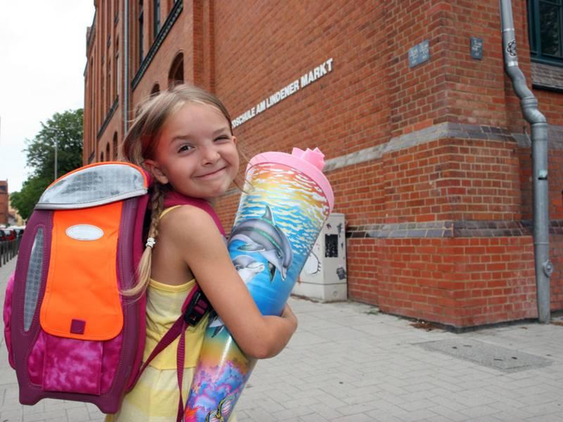 Mädchen mit Schultüte vor einem Schulgebäude