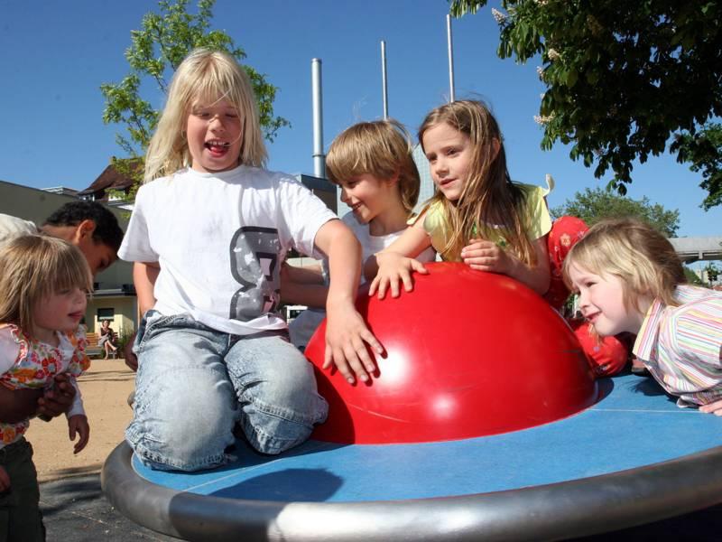 Fünf Kinder auf einer Kreisel-Scheibe auf einem Spielplatz.