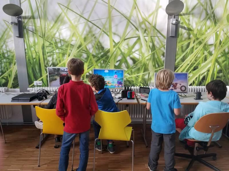 Fünf Kinder, teils stehend, teils sitzend, spielen verschiedene digitale Spiele auf drei Bildschirmen.