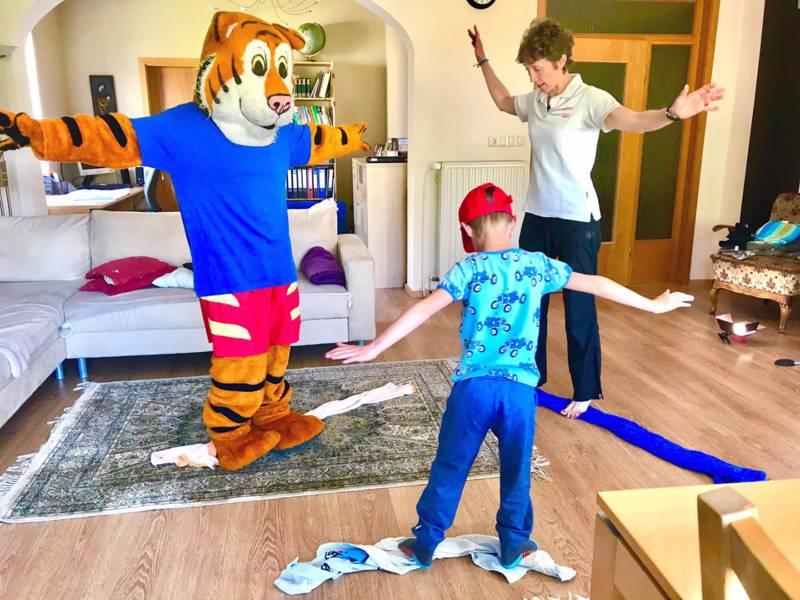Ein Kind, eine Frau und eine Person in Tigerkostüm machen Sportübungen in einem Wohnzimmer.