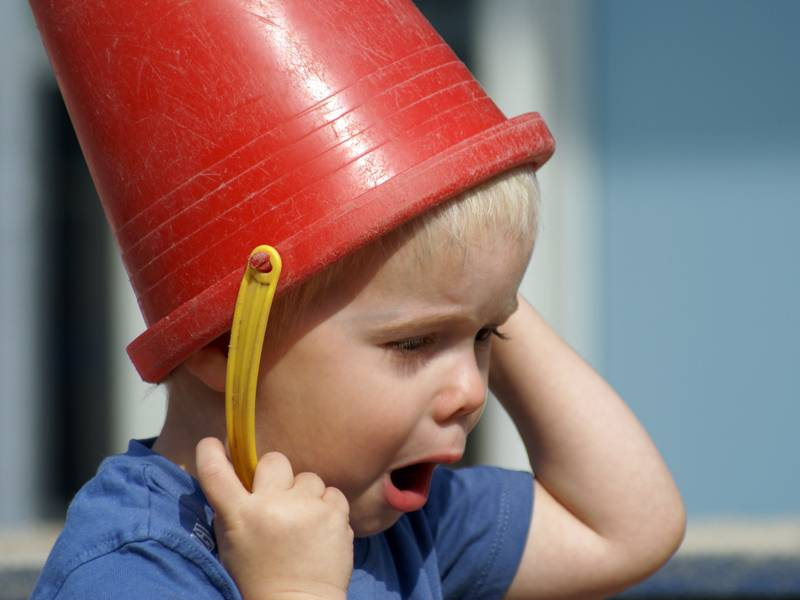 Ein Kind stülpt sich einen roten Eimer über den Kopf.