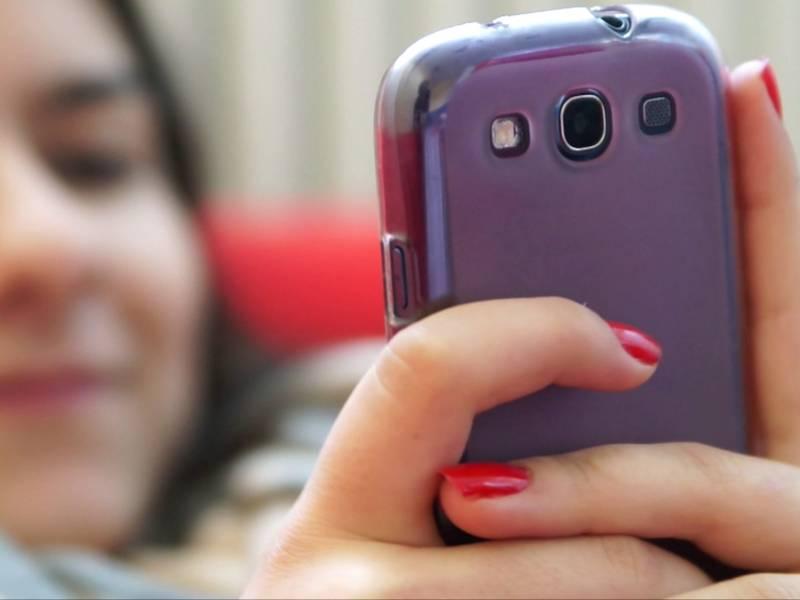 Junge Frau filmt sich mit ihrem Handy