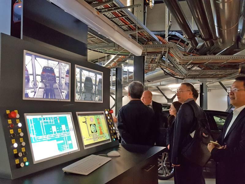 In der Autostadt: Mehrere Personen in einem Kontrollraum mit vier Monitoren und einem Auto im Hintergrund