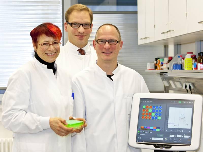 Drei Menschen im weißen Kittel in einem Labor.
