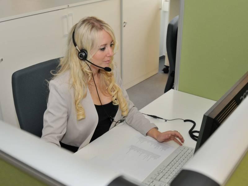 Eine blonde Frau mit Headset am Computer