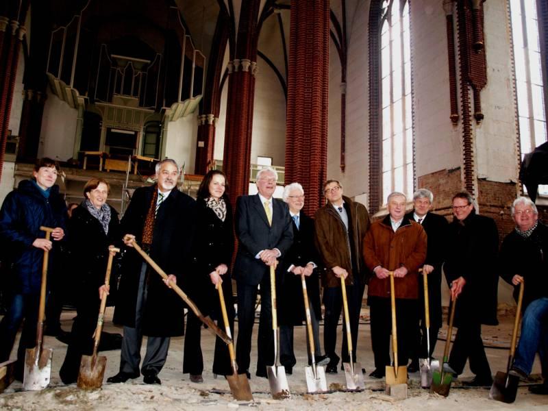 Elf Männer und Frauen in einem Altarraum mit einem Spaten in der Hand.