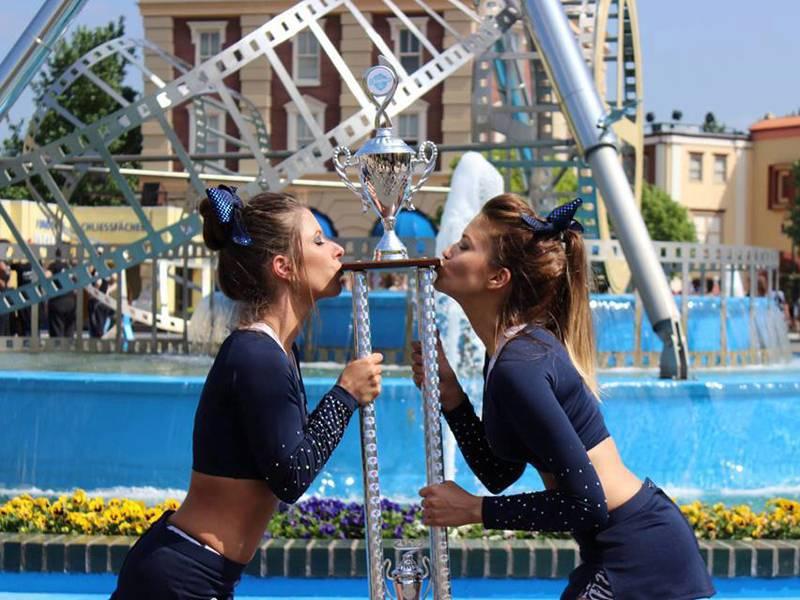 Zwei Cheerleaderinnen küssen eine große Trophäe.