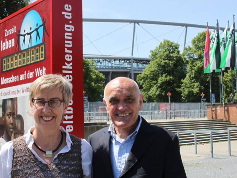 Eine Frau und ein Mann stehen vor der Weltbevölkerungsuhr, im Hintergrund die AWD-Arena.