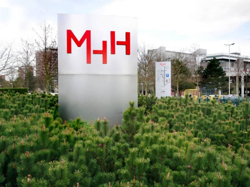 Stele mit dem Schriftzug MHH inmitten von Bäumen, daneben ein Parkplatz.
