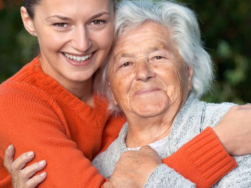 Eine junge und eine alte Frau halten sich in den Armen