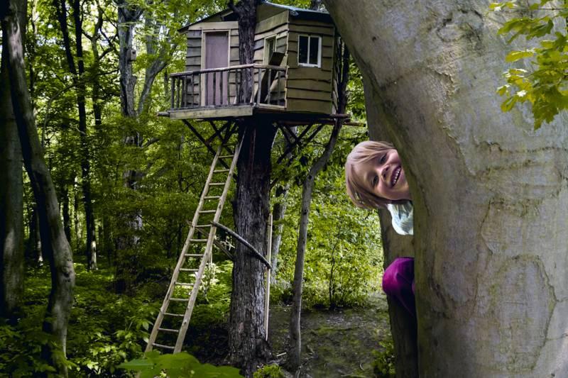 Kind schaut vor einem Baumhaus hinter einem Baum hervor.