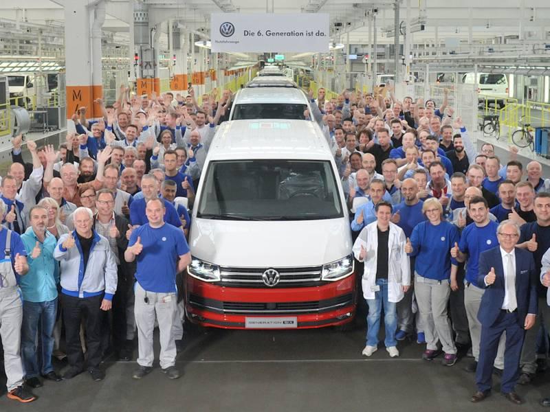 Menschen mit VW-Transporter in Produktionshalle