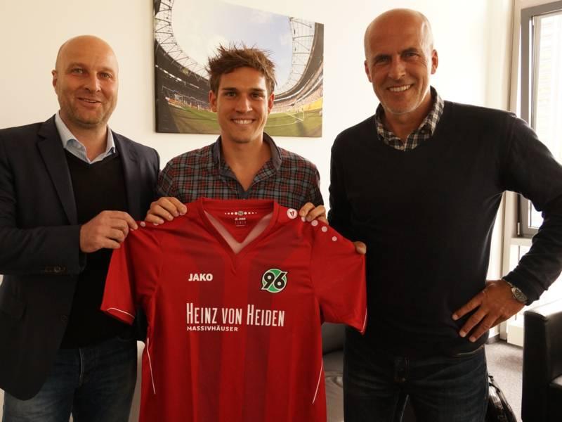 Drei Männer stehen in einer Reihe. Der jüngste in der Mitte hält ein Trikot von Hannover 96 in den Händen.