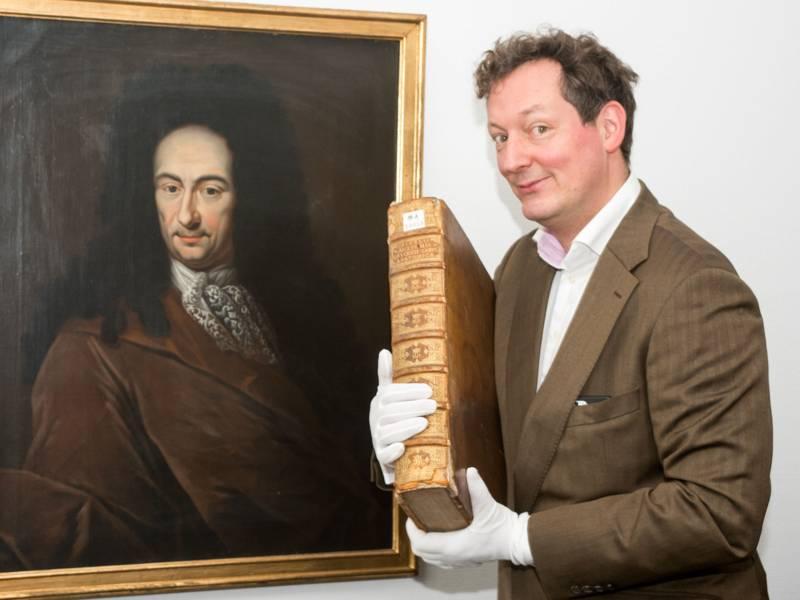 Mann mit voluminösen, alten Bild im Arm vor einem historischen Gemälde