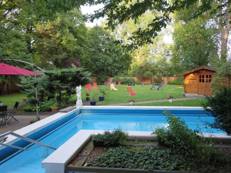 Ein Garten mit mehrere Liegen, Pool und kleinem Häuschen.