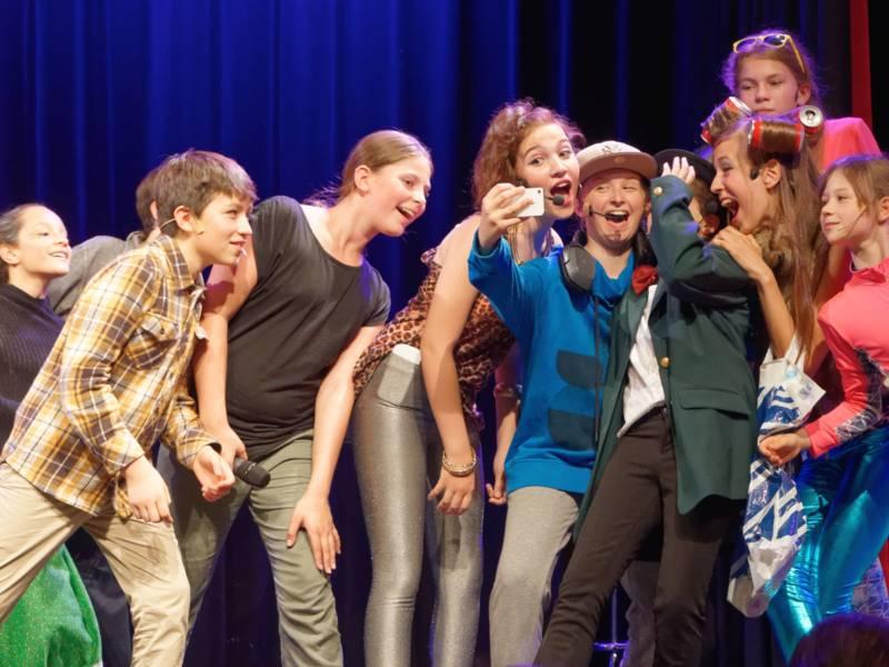 Kinder auf einer Bühne, die ein Selfie von sich schießen.