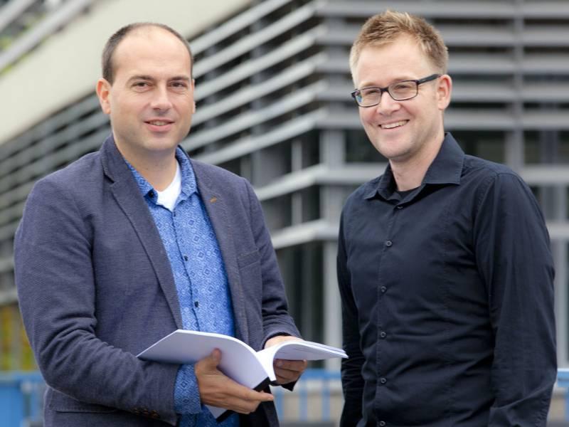 Zwei Männer, der linke hält ein aufgeschlagenes Buch in den Händen.