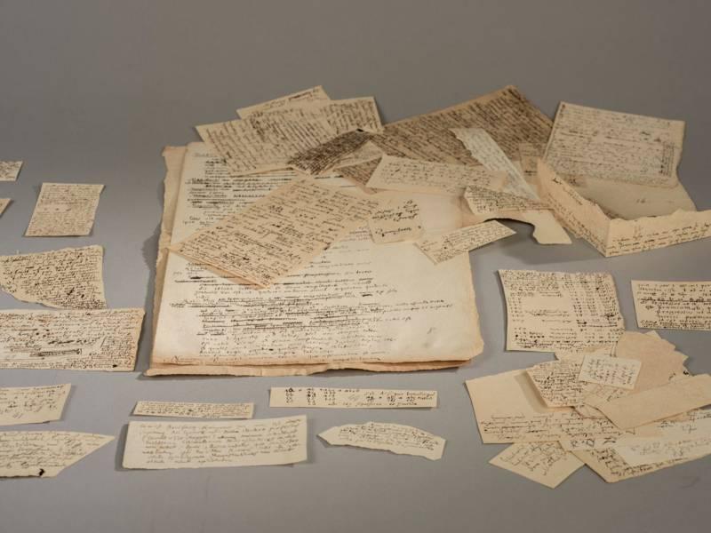 Mehrere Papierschnipsel mit einer altertümlichen Schrift.