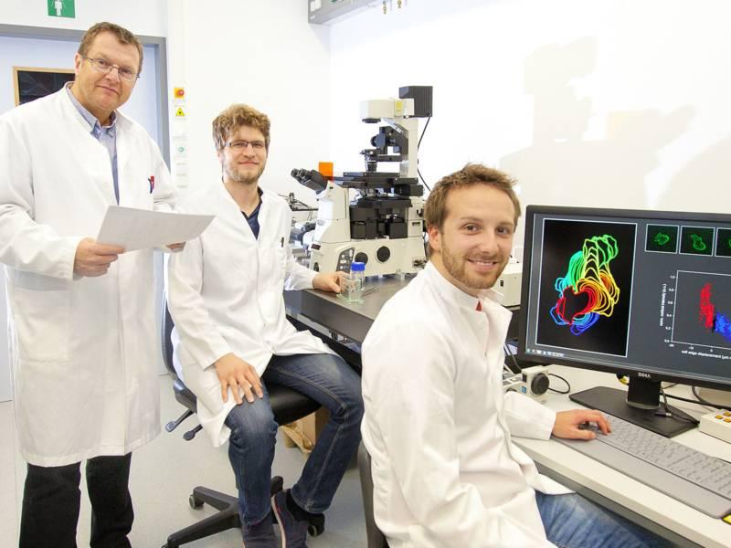 Drei Männer in weißen Kitteln vor einem Computerbildschirm und/oder Mikroskop.